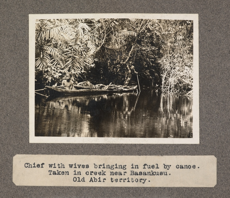 Chief with wives bringing in fuel by canoe. Taken in creek near Basankusu. Old Abir territory