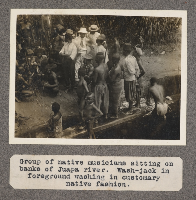 Group of native musicians sitting on banks of Juapa River. Wash Jack in foreground washing in customary native fashion